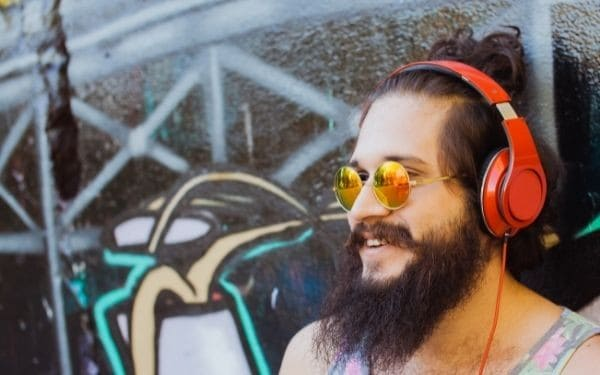 Man wearing sunglasses and red over ear headphones