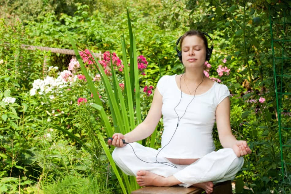 Pregnant lady meditating with headphones on in the garden
