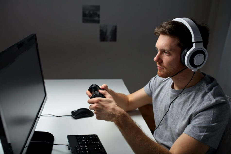 Gamer with white headset in front of black screen
