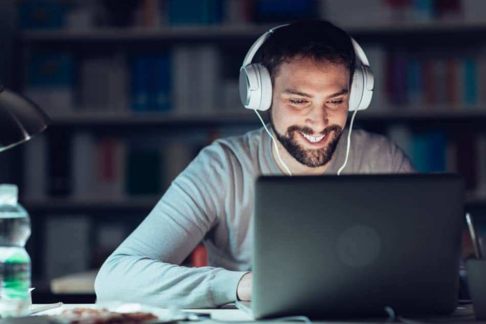 Man with over ear headphones working on laptop